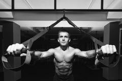 Allenamento dell'uomo di forma fisica sugli anelli nella palestra Fotografia Stock