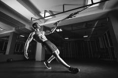 Allenamento dell'uomo di forma fisica sugli anelli nella palestra Immagine Stock
