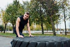 Allenamento dell'uomo di sport di forma fisica all'aperto con la gomma del trattore Fotografie Stock