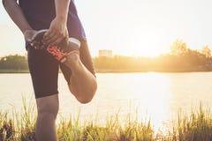 Allenamento dell'uomo e concetto di benessere: Riscaldamento asiatico del corridore il suo corpo Fotografia Stock