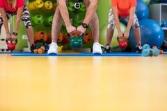 Allenamento dell'uomo e della donna di esercizio dell'oscillazione di Kettlebells alla palestra Immagini Stock