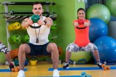 Allenamento dell'uomo e della donna di esercizio dell'oscillazione di Kettlebells alla palestra Immagine Stock