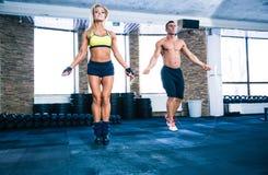 Allenamento dell'uomo e della donna di forma fisica con la corda di salto Fotografie Stock Libere da Diritti