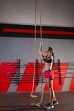 Allenamento della donna di esercizio di salita della corda alla palestra Fotografie Stock