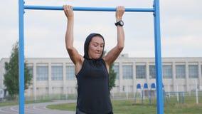 Allenamento della donna di forma fisica che fa gli esercizi su una barra orizzontale all'aperto video d archivio