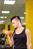Allenamento della donna di forma fisica con la testa di legno arancio Immagini Stock