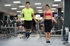 Allenamento della donna e dell'uomo con la corda di salto nella palestra del crossfit Fotografie Stock