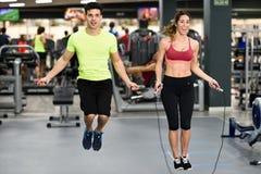 Allenamento della donna e dell'uomo con la corda di salto nella palestra del crossfit Fotografia Stock