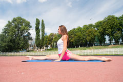 Allenamento della donna ed allungare sulla stuoia di forma fisica Immagine Stock