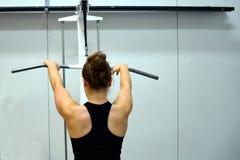 Allenamento della donna i suoi muscoli dorsali e armi Immagini Stock Libere da Diritti