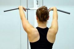 Allenamento della donna i suoi muscoli dorsali e armi Fotografie Stock