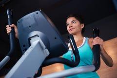 Allenamento della donna sulla macchina di esercizi Fotografie Stock