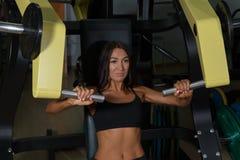 Allenamento della donna sulla macchina di esercizio nella palestra di sport Fotografie Stock Libere da Diritti