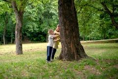 Allenamento della famiglia - generi ed i suoi bambini che fanno l'yoga nel parco fotografia stock libera da diritti
