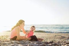 Allenamento della famiglia - madre e figlia che fanno gli esercizi sulla spiaggia Immagini Stock Libere da Diritti