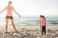 Allenamento della famiglia - madre e figlia che fanno gli esercizi sulla spiaggia Immagine Stock Libera da Diritti