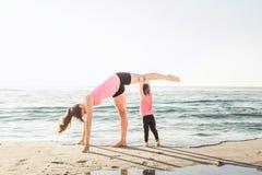 Allenamento della famiglia - madre e figlia che fanno gli esercizi sulla spiaggia Fotografie Stock