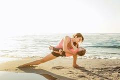 Allenamento della famiglia - madre e figlia che fanno gli esercizi sulla spiaggia Fotografie Stock Libere da Diritti