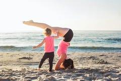 Allenamento della famiglia - madre e figlia che fanno gli esercizi sulla spiaggia Immagine Stock