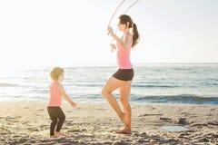Allenamento della famiglia - madre e figlia che fanno gli esercizi sulla spiaggia Immagini Stock