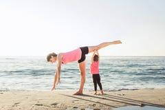 Allenamento della famiglia - madre e figlia che fanno gli esercizi sulla spiaggia Fotografia Stock