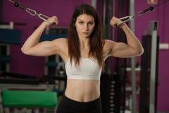 Allenamento della giovane donna di Actove le sue armi nella palestra del club di forma fisica Fotografie Stock