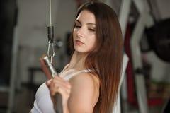 Allenamento della giovane donna di Actove le sue armi nella palestra del club di forma fisica Fotografia Stock
