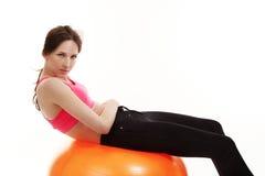Allenamento della giovane donna su una sfera arancione di forma fisica Fotografie Stock