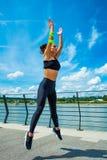 Allenamento della giovane donna sul outd di salto di configurazione muscolare e dello strainght Fotografia Stock Libera da Diritti