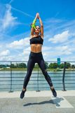 Allenamento della giovane donna sul outd di salto di configurazione muscolare e dello strainght Immagini Stock Libere da Diritti