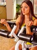 Allenamento della ragazza sulla macchina del ricciolo del bicipite nella palestra di sport Fotografie Stock
