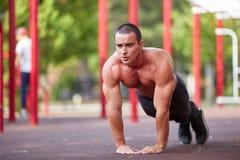 Allenamento della via - allenamento muscolare bello dell'uomo nel parco Fotografia Stock
