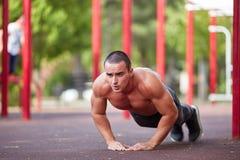 Allenamento della via - allenamento muscolare bello dell'uomo nel parco Fotografia Stock Libera da Diritti