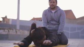 Allenamento delle coppie all'aperto La donna ispana che fa indietro solleva la menzogne sullo stomaco sulla stuoia nella zona urb archivi video