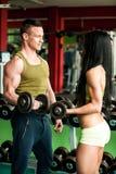 Allenamento delle coppie di forma fisica - l'uomo e la donna adatti si preparano in palestra Immagini Stock
