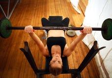 Allenamento di addestramento della donna di forma fisica che fa gli edifici occupati con il bilanciere in palestra Immagini Stock