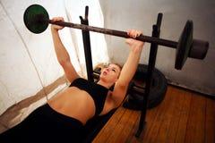 Allenamento di addestramento della donna di forma fisica che fa gli edifici occupati con il bilanciere in palestra Fotografia Stock Libera da Diritti