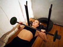Allenamento di addestramento della donna di forma fisica che fa gli edifici occupati con il bilanciere in palestra Fotografia Stock