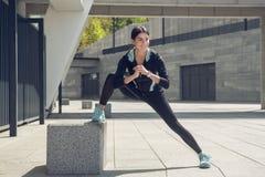 Allenamento di esercizio attivo della giovane donna sulla via all'aperto Immagine Stock