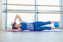 Allenamento di esercizio della palla di stabilità della donna di Pilates alla palestra dell'interno Fotografia Stock