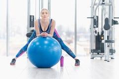 Allenamento di esercizio della ragazza della giovane donna nella palestra facendo uso della palla Fotografie Stock