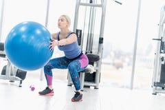 Allenamento di esercizio della ragazza della giovane donna nella palestra facendo uso della palla Fotografia Stock Libera da Diritti
