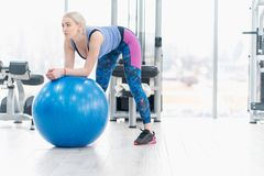 Allenamento di esercizio della ragazza della giovane donna nella palestra facendo uso della palla Fotografia Stock