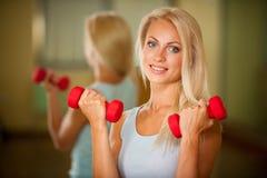 Allenamento di forma fisica - addestramento adatto della donna con il dumbellc in palestra Immagine Stock Libera da Diritti