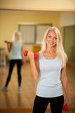 Allenamento di forma fisica - addestramento adatto della donna con il dumbellc in palestra Immagini Stock