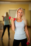 Allenamento di forma fisica - addestramento adatto della donna con il dumbellc in palestra Fotografia Stock