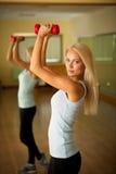 Allenamento di forma fisica - addestramento adatto della donna con il dumbellc in palestra Fotografia Stock Libera da Diritti