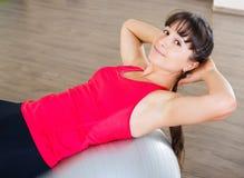 Allenamento di forma fisica della giovane donna in palestra con fitball Fotografie Stock