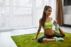 Allenamento di forma fisica Esercizi di pratica di yoga della donna che allungano a casa Immagini Stock