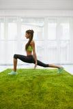 Allenamento di forma fisica Esercizi di pratica di yoga della donna che allungano a casa Immagine Stock